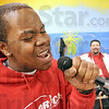 Crooner: Antaiwan Donigan sings karaoke in the Alorica break room Tuesday afternoon. D.J. Eric Hite watches at right.