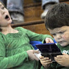 Tech savy: Three-year-old Talan Boehler (R) and his eight-year-old sister Morgan occupy themselves with video games during the West Vigo vs. Brown Co. game at the tip-off  of the Plainfield sectional. Their father is the West Vigo coach Anthony Boehler.