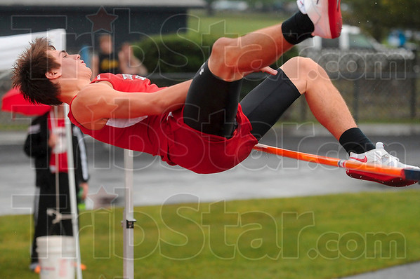 Knocking off the rain drops: Terre Haute South's Nicholas Jaeger brushes the bar as he overcomes a height of six feet and two inches during the high jump competition of the boys track sectional Thursday at North.