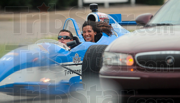 Tribune-Star/Joseph C. Garza<br /> Street legal: Indianapolis 500 Princess and Terre Haute native Brittany Dorsett enjoys a ride in an Izod IndyCar series two-seat racecar that was driven by Grant Richey Thursday on Fort Harrison Road.