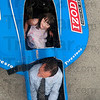 Tribune-Star/Joseph C. Garza<br /> The racecar kid: Five-year-old Taryn Kennedy giggles as she slides down into the passenger seat of a 1997-98 Dallara IndyCar with a Honda engine Thursday at Larry Paul tanning salon. The racecar was on hand as part the Izod IndyCar series tour across the state.