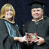 Distinguished Alumni: Barry S. Nicoson receives the Distinguished Alumni Award from Mrs. Beck Miller, Executive Director of Resource Development at Ivy Tech during Thursday's graduation ceremony.