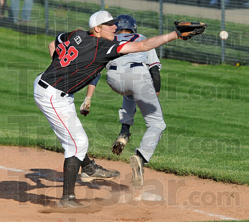 Safe: North's #17, Parker Fulkerson makes it safely to first base as the throw is wide during game action at Terre Haute South Thursday evening. South's #58, A.J. Reed can't get to the ball on the play.