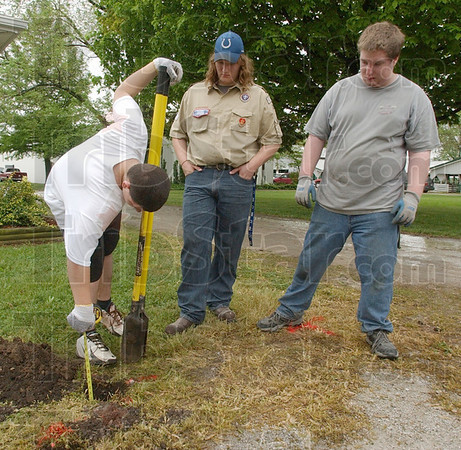 Not far to go: Dakota Gaskin measures the depth of a post hole he is digging under the supervision of his brother Michael, center. Matthew Lorey was also helping on the project.