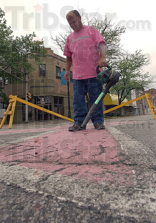 Have to wait: Gary Buck cleans the old paint job on the pink ribbon at 6th and Wabash Sunday afternoon. Due to the wet weather the application of a new coat of paint had to wait.
