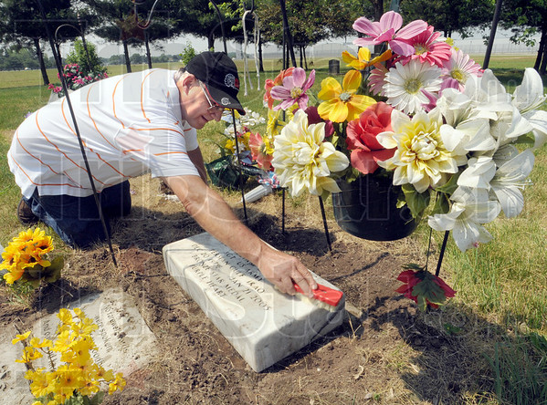 Father's love: Keith Childress cleans the Durham Cemetery grave marker of his son Sgt. Kyle Childress who was killed in Iraq in 2005.