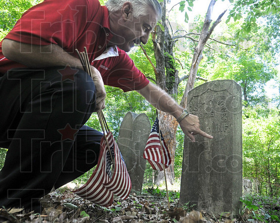 Civil War: Lost Creek Twp. Trustee Rick Long puts a flag on the gravesite of a Civil War soldier Friday afternoon at the Swalls Cemetery.
