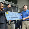 "Thumbs up: Terre Haute Children's Museum director Lynn Hughes gives the ""thumbs up"" as she receives a check for ten thousand dollars from Best Buy general manager Mike Piotrowski during the grand opening ceremony Friday morning."