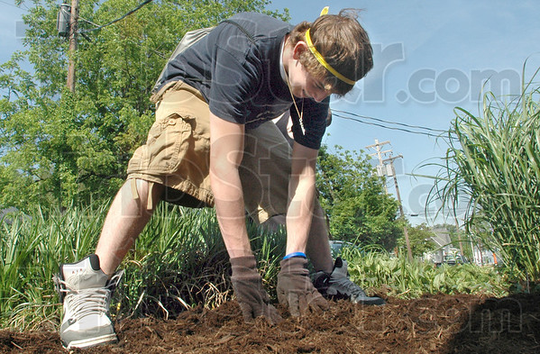 Can you dig it: McLean High School student David Mize spreads mulch in a flower bed on campus Friday afternoon. Students took time from their day to work outside on campus grounds making improvements.