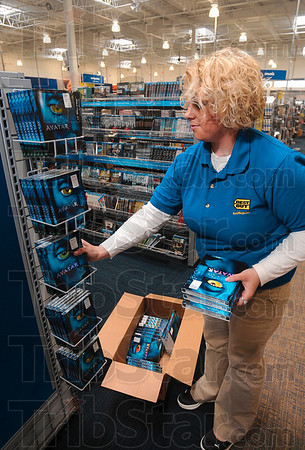 Tribune-Star/Joseph C. Garza<br /> Made in Terre Haute: Best Buy Customer Solution Specialist Maria Hirtzer places copies of the movie, Avatar, on a display in the store Thursday in preparation for the new retailer's grand opening May 21.