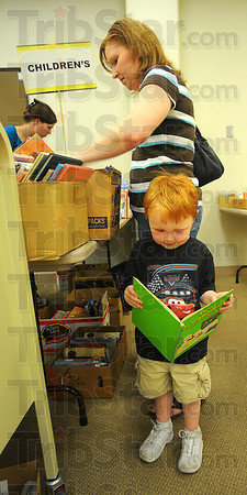 Found one: Greysen Hollifield looks through a book while his mother Tabatha searches through boxes of children's books at the Vigo County Public Library book sale Saturday. The sale continues from 1-4:00p.m. today.