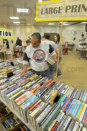 "Borrowed and bought: Tom Quintanna looks over books to purchase in the Vigo County Library book sale Saturday afternoon. He holds books from upstars that he is checking out. He was looking for works of fiction by by Patterson and Clancy as well as Robin Cooks' writings ""for the medical side""."