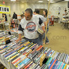 """Borrowed and bought: Tom Quintanna looks over books to purchase in the Vigo County Library book sale Saturday afternoon. He holds books from upstars that he is checking out. He was looking for works of fiction by by Patterson and Clancy as well as Robin Cooks' writings """"for the medical side""""."""
