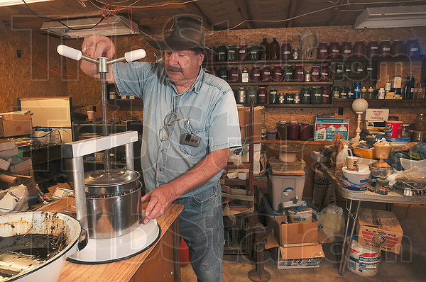 Tribune-Star/Joseph C. Garza<br /> Handmade remedy: Herbalist Jerry Bollinger uses an herb press to make a salve to treat poison ivy at his home in Coalmont Wednesday.