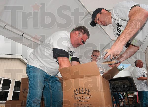 Tribune-Star/Joseph C. Garza<br /> Relief effort: Volunteers Brad Branam and Matt Millington pack bags of rice as part of a relief effort for Haiti Saturday at Cross Lane Community Church.