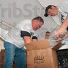 Tribune-Star/Joseph C. Garza<br /> Relief effort: Volunteers Brad Branam and Matt Millington pack bags of rice as part of a relief effort for Haiti Saturday at Cross Lane Community Church.