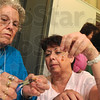 Tribune-Star/Joseph C. Garza<br /> Crafts at camp: Camp Bluebird volunteer Cathy Atterson, center, works with camp attendee Mary Ann Whallon as Whallon crafts a piece of jewelry Saturday at Camp Wabashi.