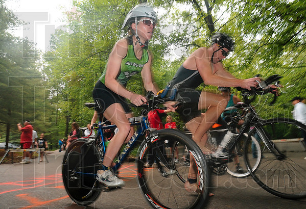 Tribune-Star/Joseph C. Garza<br /> Off to the (bike) races: Triathlete Amber Kardosh and a fellow competitor take off from the mounting line at the start of the cycling portion of the Terre Haute Triathlon Saturday, May 22 at Hawthorn Park.