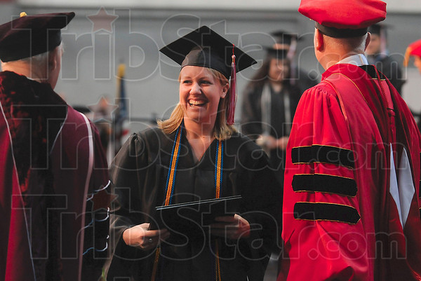 Tribune-Star/Joseph C. Garza<br /> Exit stage laugh: Rose-Hulman graduate Darcie Thomas of Brighton, Mich., shares a laugh with Peter Gustafson, left, Vice President for Student Affairs and Dean of Students, after she accepted her diploma from President Matt Branam, right, Saturday during the school's 132nd commencement.