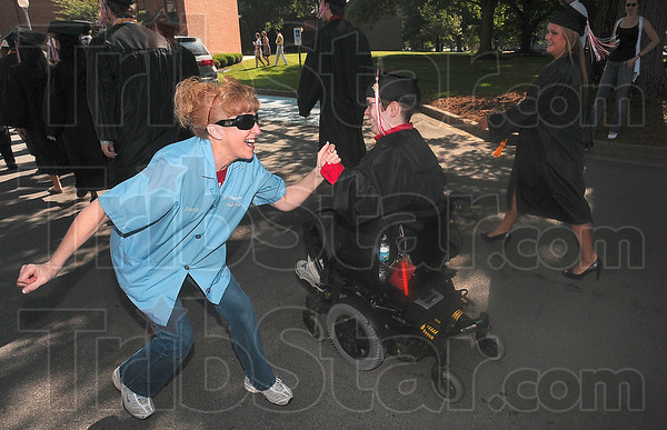 "Tribune-Star/Joseph C. Garza<br /> Sad to see them go: Rose-Hulman housekeeping staff member Nancy Randall congratulates graduating biomedical engineering major Elaine Houston as Houston passes by in the graduation procession before commencement Saturday. ""We grow close to the students,"" said Randall's co-worker, Barbara Kingery. ""They are like are kids."""