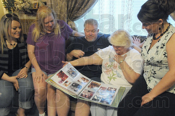 Mother's Day gift: Mike Decker sits with his mother and sisters looking at a scrap book he brought to show his newfound family Friday afternoon. MIke's sisters are from left, Sarrah Selph, Dianna Hough and Tiffany Long (far right). Mike's mother Sharon Keegan holds the book.