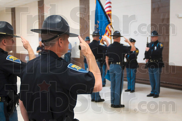 Tribune-Star/Joseph C. Garza<br /> Salute the fallen: Indiana State Police Sgt. Tom Hannon salutes with his fellow troopers as Taps is played by Terre Haute South students Andrew Keiser and Cody Pratt during a memorial ceremony Wednesday at the operating engineers union on US 41.