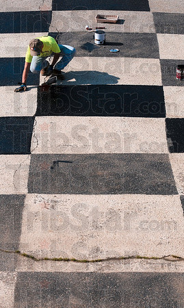 Tribune-Star/Joseph C. Garza<br /> Duke Energy substation construction manager, Charlie Wheat, paints a checker pattern at the Terre Haute Action Track Wednesday as part of the Duke Energy Global Service Event.