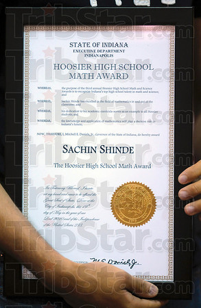 Tribune-Star/Joseph C. Garza<br /> A second plaque for his wall: Terre Haute South senior Sachin Shinde holds his Hoosier High School Math Award after it was presented to him by Gov. Mitch Daniels Wednesday at South.
