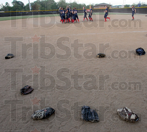Celebration: Softball gloves lay scattered on the sidelines as Patriots celebrate on the pitchers' mound after their 2-0 win in the sectional championship game Wednesday evening.