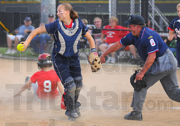 Taking care of business: Patriot catcher Kelsey Coffey tosses the ball to the pitchers' mound after tagging out Terre Haute South baserunner Dana Hedden to end the inning. Umpire Dave Bogard makes the call.