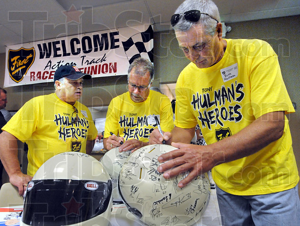 Hulman Heroes: Former Action Track drivers Steve Carson, Kin Jacobs and Keith Kaufmann sign helmets prior to Wednesday's luncheon event.