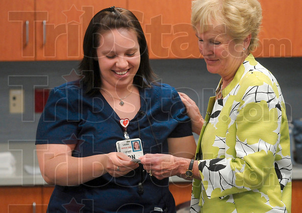 Tribune-Star/Joseph C. Garza<br /> For the caregivers: Union Hospital RN Laura Livingston receives a Guardian Angel pin from Jo Einstandig, the wife of former patient, Jerry Einstandig, during a presentation Monday at the hospital.