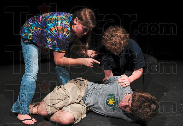 Tribune-Star/Joseph C. Garza<br /> Duped: Slave traders portrayed by Terre Haute North seniors Kary Kirchner and Luke Lakstins inform a man entrapped in human trafficking played by senior Elliot Menge that they own him during rehearsal for the play, No Evil, Monday at Terre Haute North.