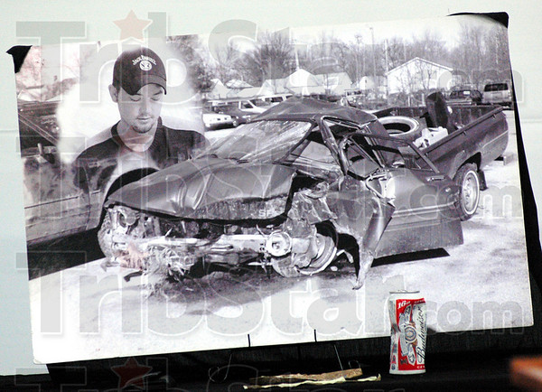 Crash: A black and white photograph of the vehicle Travis was driving at the time of his death and a crushed beer can that was taken from the vehicle after the crash tell the story.