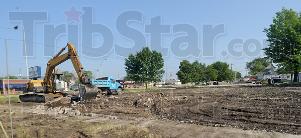 Corner clean-up: An excavator removes the remnants of a house located in the 1800 block of South Third Street Tuesday morning. The former car wash and other buildings on the southeast corner of the block have been removed.