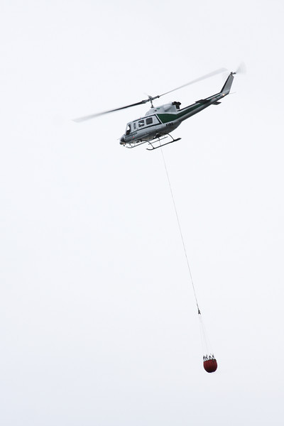 Forestry's helicopter swings by with a bucket for the fire.