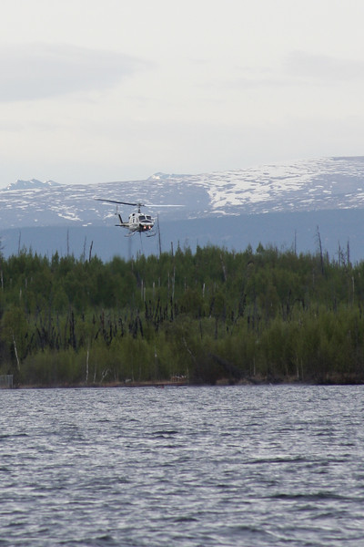 The Division of Forestry's helicopter drops low to fill a bucket to aid in the fire's suppression.