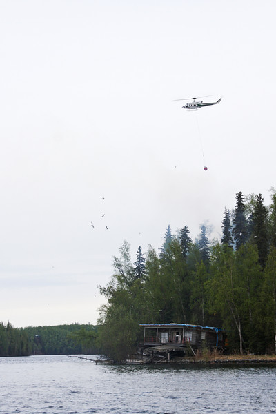 Forestry patrols overhead in their helicopter as crews on the ground move in and begin knocking down the fire.