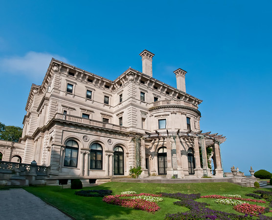 The Breakers is a Vanderbilt mansion located in Newport, Rhode Island. It is a National Historic Landmark. The Breakers was built as the Newport summer home of Cornelius Vanderbilt II, a member of the wealthy United States Vanderbilt family. Designed by renowned architect Richard Morris Hunt and with interior decoration by Jules Allard and Sons and Ogden Codman, Jr., the 70-room mansion boasts approximately 65,000 sq ft (6,000 m2). of living space. The home was constructed between 1893 and 1895 at a cost of more than $7 million (approximately $150 million in today's dollars adjusted for inflation). The Ochre Point Avenue entrance is marked by sculpted iron gates and 30-foot (9.1 m) high walkway gates are part of a 12-foot-high limestone and iron fence that borders the property on all but the ocean side. The 250' x 120' dimensions of the five-story mansion are aligned symmetrically around a central Great Hall. Part of a 13-acre (53,000 m²) estate on the seagirt cliffs of Newport, it sits in a commanding position that faces east overlooking the Atlantic Ocean. [from Wikipedia]
