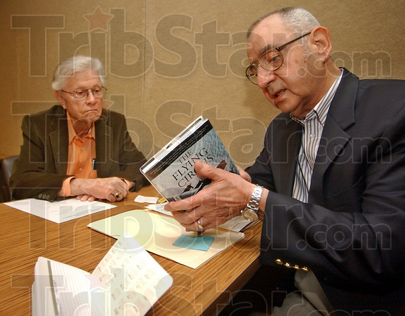 """Looking back: Con Harrold and Elmer Ciancone look over the book """"The Flying Circus"""" . The book chronicles flying during WWII in the Pacific theatre. The two belong to Military Officers Association of America."""