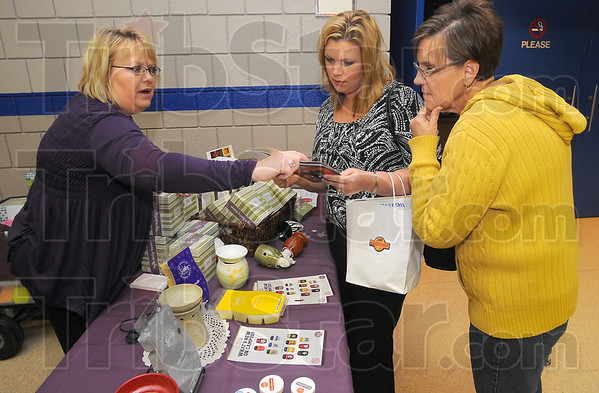 Smell of success: Brenda Walker, an independant consultant with Scentsy Wickless, talks about her products with Hope Massey and Cheryl Hutchison before the Taste of Home Cooking program at Hulman Center Thursday evening.