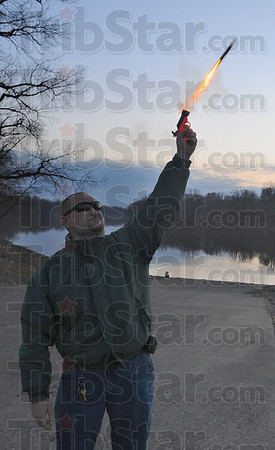 Screamer: Matt Christie fires a noise maker out over the Wabash River at the Fairbanks Park boat launch Thursday evening. The group of crow chasers are tying to guide the crow population into areas where they'll have as little impact as possible.