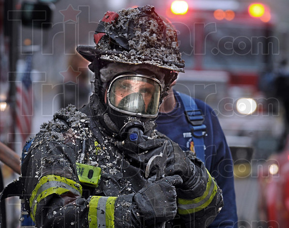Insulation: A Terre Haute firefighter emerges from the scene of a fatal house fire Thursday afternoon covered with fallen insulation. Firefighters found the body of an elderly man inside the burned-out residence.