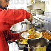 Full meal deal: Covie Hurtt prepares a dinner plate at the Bethany House soup kitchen Thursday afternoon.