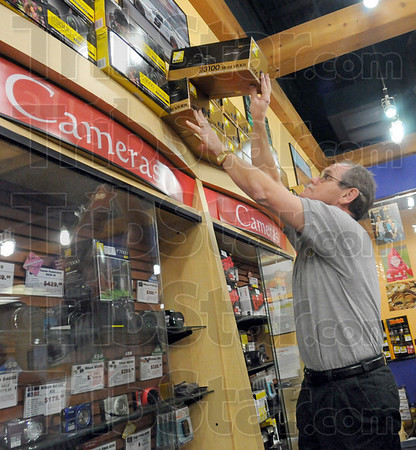 Picture this: Ray Klotz of Galloway Photo stocks the shelves with digital cameras for Black Friday's start to the Christmas shopping season.