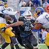Pressure: Sycamore lineman Ben Obaseki(92) is held by Jacks defender Ryan McKnight(60) as Larry Carter puts a hit on quarterback Thomas O'Brien.