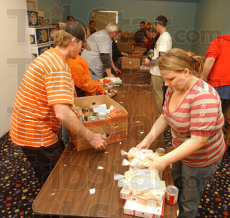 Sharing: Shannon Kirkman and Caitlyn Phegley load Thanksgiving baskets with others at Club Soda Sunday afternoon. The organization will distribute 90 baskets this year, up from the 75 last year.