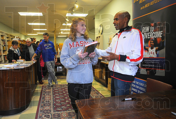 """Author, author: Cassidy Hass talks with Meb Keflezighi at teh Boob Nation bookstore Sunday afternoon. MArathon champion Keflezighi was signing copies of his book """"Run to Overcome""""."""