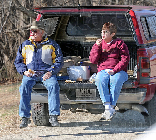 Tailgate snack: Bob and Carol Mountjoy of Brazil enjoy a snack while tailgating at the Bridgeton Mill Dam watching heavy water flow over the falls Sunday afternoon.