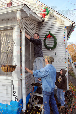 All is merry and bright: Quinton Brady strings Christmas lights around a front porch window withr his friend Danny Compton and Compton's grandson Ilasha Young at Compton's southside home.